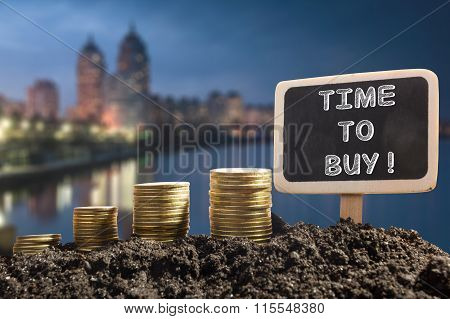 Time to buy - Financial opportunity concept. Golden coins in soil Chalkboard on blurred urban backgr