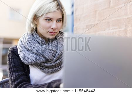 Focused woman working with laptop outdoor at cafe