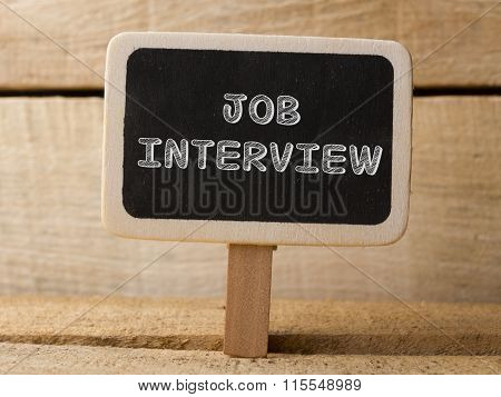 Chalkboard on wooden background with Job Interview words