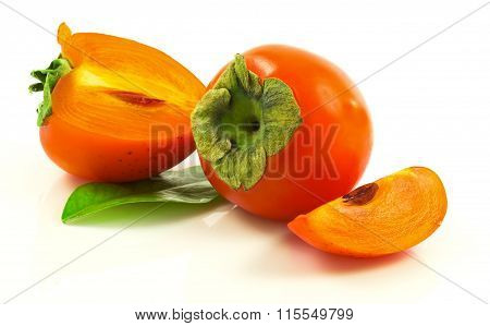 Group Of Ripe Fresh Persimmons With Slices And Leaves