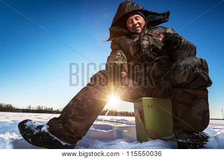 Mature man fishing on the winter lake