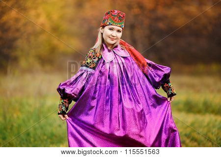 Beautiful pretty girl in national bright purple dress with red kerchief on her head, ornaments and e