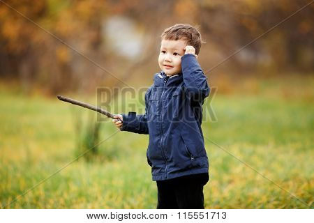 Cute boy with wooden stick in his hand playing at autumn park outdoors. Confused, thinking what to d