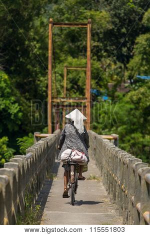 Indonesian woman in traditional hat riding her bicycle across the bridge