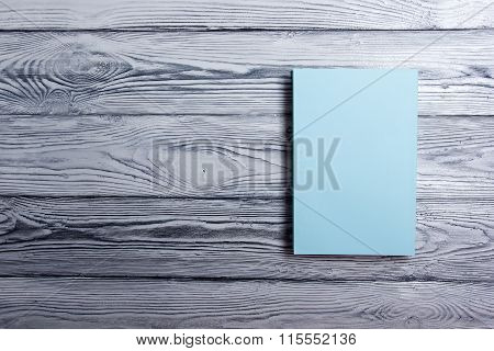 Blank book cover on textured wood background. Copy space