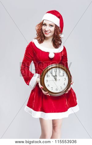 Christmas Time Concept. Smiling Gleeful Sexy Red Haired Santa Helper Posing With Big Round Clock