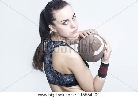 Sport Concepts. Female Athlete Posing With American Football Ball. Looking Backwards.against White.