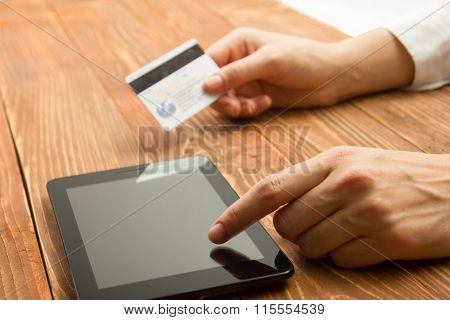 Hands holding credit card typing numbers on tablet pc making online payment at home the wooden table