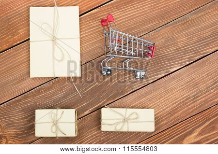 Online shopping concept - Empty Shopping Cart, laptop and tablet pc, gift box on rustic wooden backg