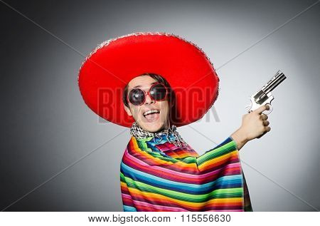 Man in vivid mexican poncho holding handgun against gray