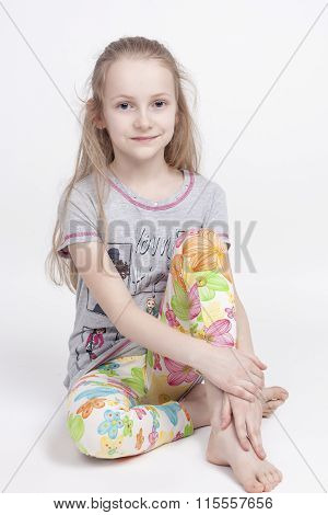 Portrait Of Nice And Cute Caucasian Blond Kid Posing Against White Background. Sitting With Hands Cr