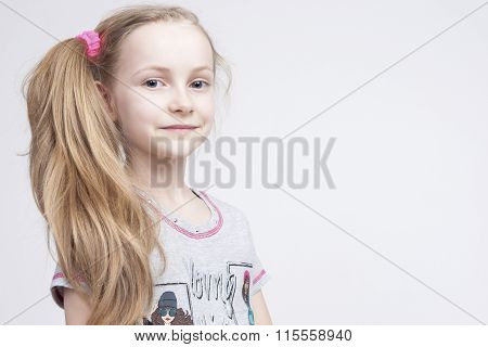 Closeup Portrait Of Cheerful Smiling Caucasian Female Blond Kid. Posing Against White Background