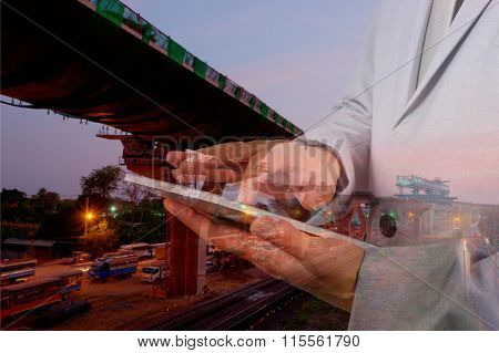 Double Exposure Of Engineer Man Use Mobile Tablet With Sunset Scene And Construction Site