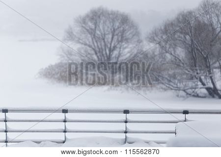 Snow-covered Balustrade And Trees On Blurred Background.