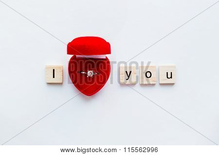 White Background With Wooden Words I Love You And Diamond Engagement Ring In Red Gift Box.