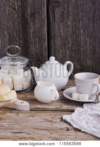 Kitchen simple still life of tea, cup, white sugar lump in a bank and fresh homemade cakes
