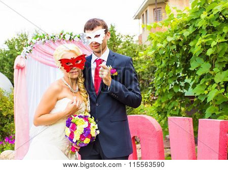 Bride and groom with funny carnival masks