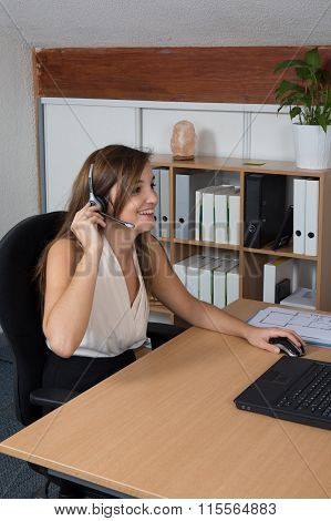Woman Wearing Headphones In Computer Room Typing And Smiling