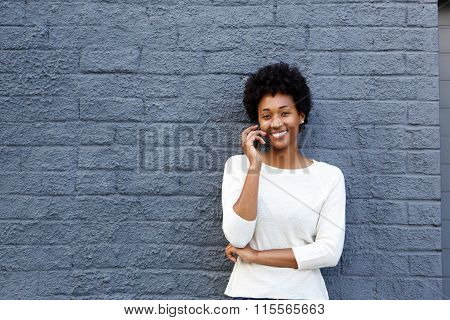 Happy African Woman Using Mobile Phone And Smiling