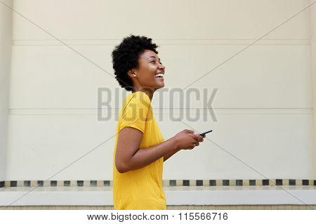 Cheerful Young African Woman Walking With A Mobile Phone