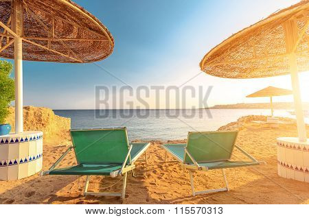Umbrellas and two empty deckchairs on the shore sand beach