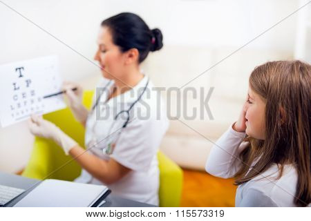 Female pediatrician pointing at eye chart to child