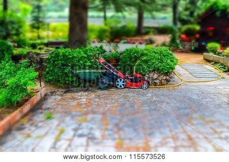 A Mower And A Wheelbarrow In The Garden