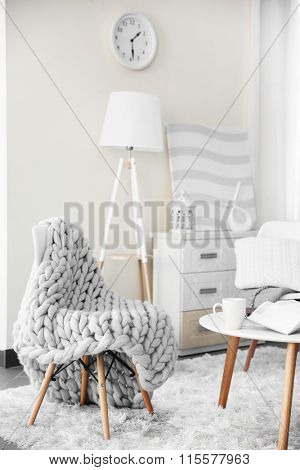 Room design with white furniture, picture, clock and floor lamp over beige wall