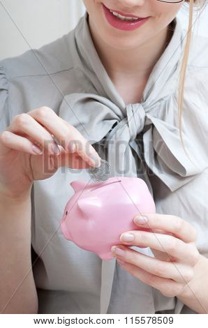 Happy Smiling Woman Inserting Coin In A Piggy Bank.