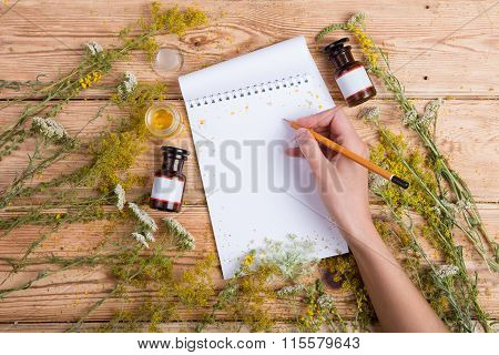 Alternative Medicine Concept - Hand Write A Recipe In Notepad On Wooden Table, Herbs Around