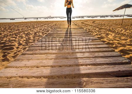 Sandy beach with shadow of running woman