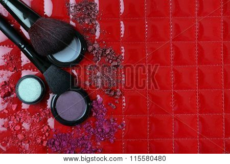 Two makeup brushes with shadows and pink rouges on red background closeup