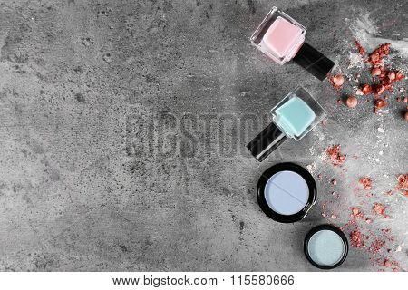 Two blue shadows with nail polish and crushed rouge on gray background