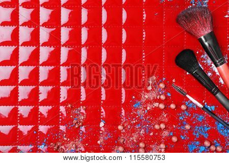 Three makeup brushes with drops of shadows and rouge on red background