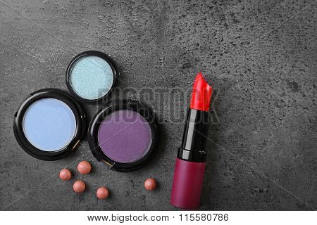 Red lipstick and blue shadows with rouge on gray background