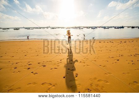 Woman running on the sandy beach