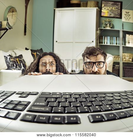 Two weird computer geeks starring at keyboard