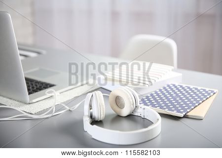 Headphones and copybooks on gray table against defocused background