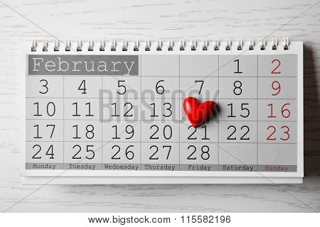 Calendar for Valentines Day with small heart on wooden background