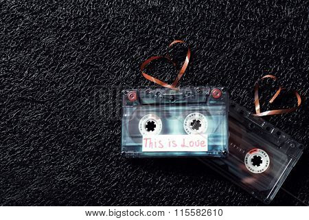 Retro audio cassettes with tapes in shape of hearts on black textured background