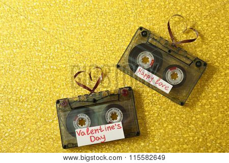 Retro audio cassettes with tapes in shape of hearts on yellow textured background