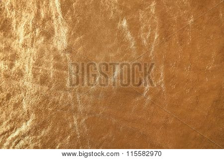 Golden leather texture with crumpled uneven surface