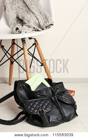 Fashion female backpack with book near white chair on a floor