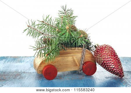 Wooden toy car with fir sprigs and cone on a table over white background