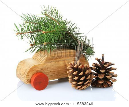 Wooden toy car with fir sprigs and cones, isolated on white