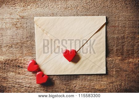 Old textured gift envelope with small heart on wooden background