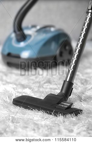 Cleaning concept - vacuum cleaner on white soft carpet, close up