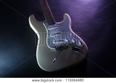 Part of electric guitar, on dark lighted background