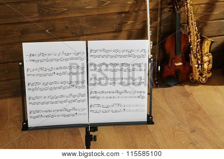 Note holder against musical instruments on wooden background