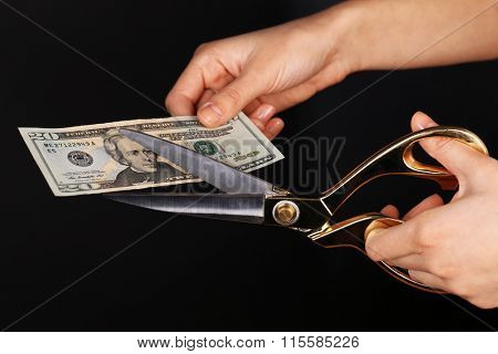 Hands with scissors cutting dollar banknote, on black background